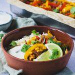 Skål med kylling fajita serveret med hvidløgsris og limedressing